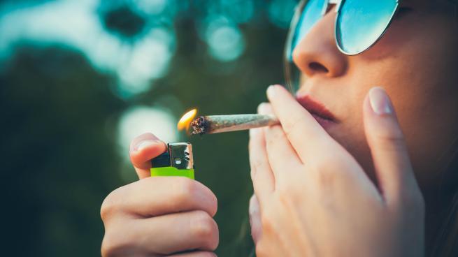 une jeune femme s'allume un joint de cannabis